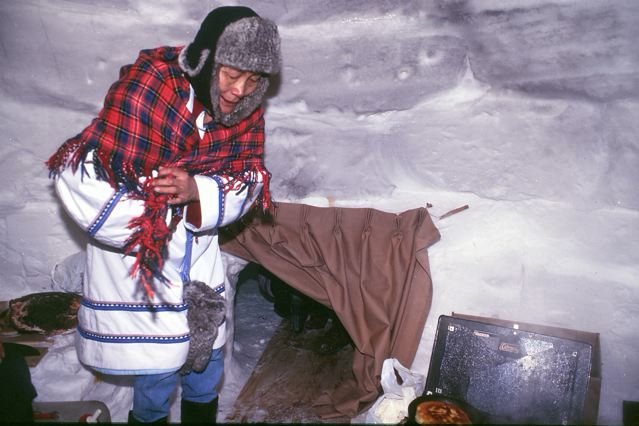 Preparing bannock in the igloo during a community celebration