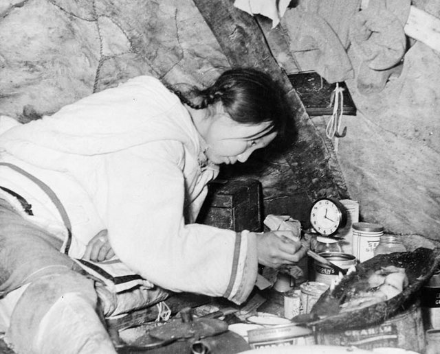Photo Inuit woman trimming seal oil lamp taken during Eastern Arctic Patrol